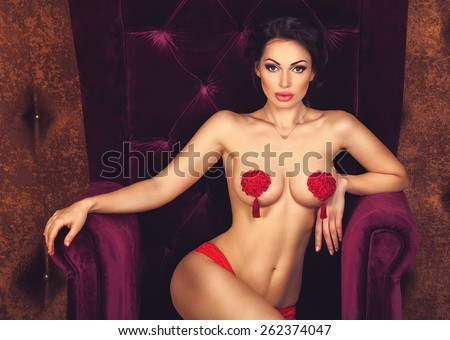 Sexy beautiful brunette woman posing sitting naked with stikini on nude breasts in a luxury velvet armchair, looking at camera - stock photo