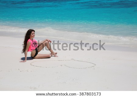Sexy beautiful girl with heart on sand in black bikini relaxing on exotic beach beside blue water by seashore. Summer vacation. Attractive young woman. - stock photo