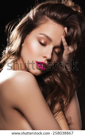 Sexy Beautiful sensual woman with bright make up, shine brown hair, red lips, and with closed eyes  - stock photo