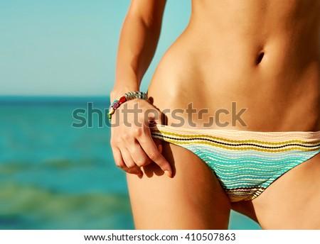 Sexy beautiful woman at the sea coast. Close up hips. Retro vintage toned image, film simulation. - stock photo