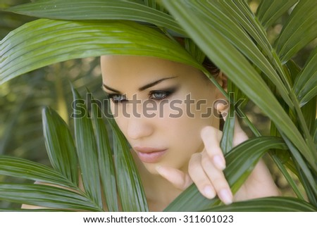 Sexy beautiful woman hiding behind the palm leaves like a panther in the tropical forest in India. Portrait of beautiful caucasian stylish young woman with smokey eyes, wildness - stock photo