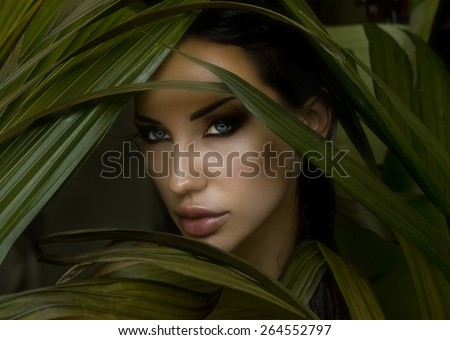 Sexy beautiful woman hiding behind the palm leaves. Portrait of beautiful stylish young woman with smokey eyes, wildness - stock photo