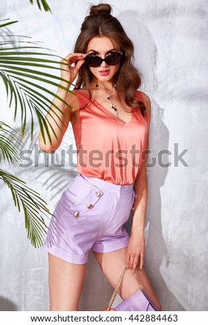 Sexy beautiful woman luxury chic fashion brand handbag trendy jewelry style for party date glamour pose summer palm clothes collection brunette hair accessory model wear silk blouse short, hairdo - stock photo
