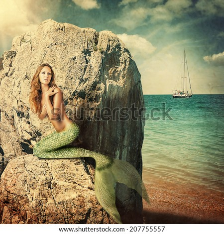Sexy beautiful woman mermaid with long tail sitting on a rock about sea. Hiding from sailboat - stock photo