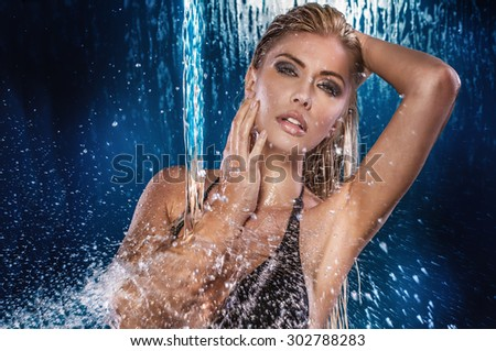 Sexy beautiful woman posing wet over water drops. Studio shot. - stock photo