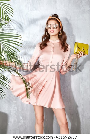 Sexy beauty woman in beige silk dress luxury chic fashion gold sunglasses brand hand bag trendy hat jewelry style for party date glamour pose summer palm clothes collection brunette hair  - stock photo