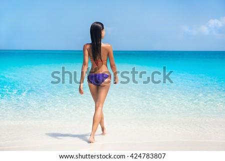 Sexy bikini body woman swimming in turquoise ocean on paradise beach in tropical destination summer Caribbean travel. Model in purple swimwear and suntan skin relaxing sunbathing on holiday. - stock photo