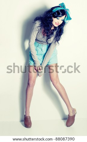 Sexy black haired pin up girl in blue shorts and wooden shoes; a lot of copyspace available; retro style image - stock photo
