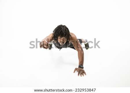 Sexy black man with dreadlocks working out wearing all black vest top and exercise shorts in a one handed press up punching one arm forwards - stock photo