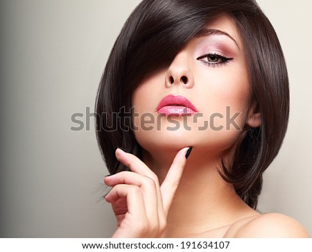 Sexy black short hair style female model looking with finger near the face. Beautiful bright makeup - stock photo