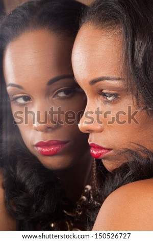Sexy black woman in black shirt, looking into a mirror - stock photo