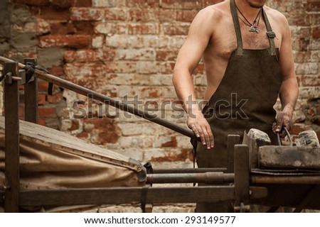 Sexy blacksmith working in the forge - stock photo