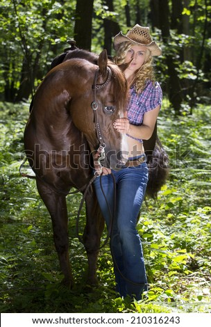 Sexy blond cowgirl with her horse in green forest. - stock photo