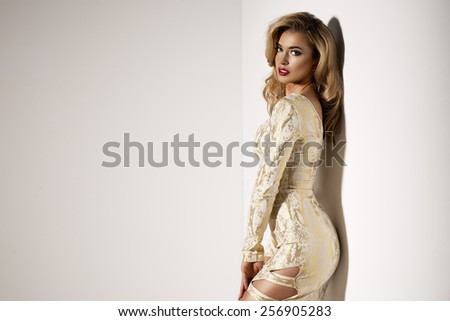 Sexy blond lady in gold dress on dark background  - stock photo