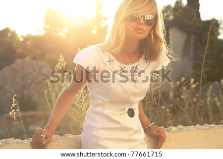 Sexy blond lady posing in sunglasses - stock photo