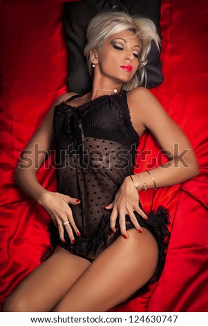 Sexy Blond Model on Red Silk Sheets wearing Black Lingerie/Sensual Dreams - stock photo