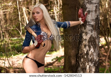 Sexy blond woman holding an axe - stock photo
