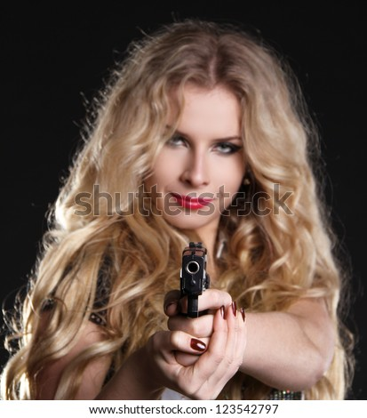 Sexy  blond woman holding gun isolated on black background - stock photo
