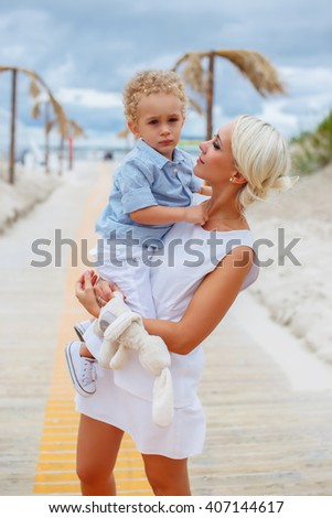 Sexy blond woman holds child on her arms. - stock photo