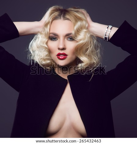 Sexy blond woman in black coat over naked body. - stock photo