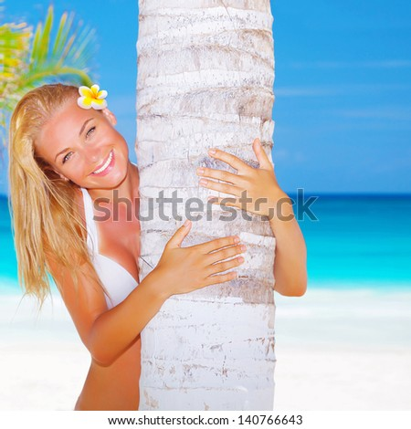 Sexy blond woman with frangipani flower in head hug palm tree on beautiful seascape background, luxury spa resort, enjoying summer vacation on the beach - stock photo