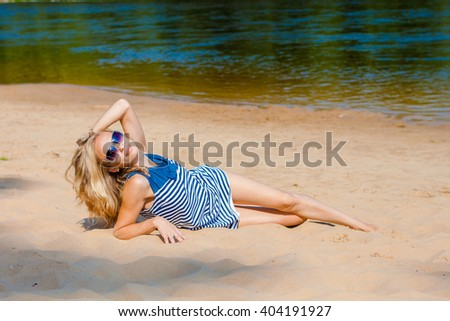 Sexy blonde bikini girl posing on beach. photo of a beautiful young woman with blowing hair relaxing on sand at a beach - stock photo