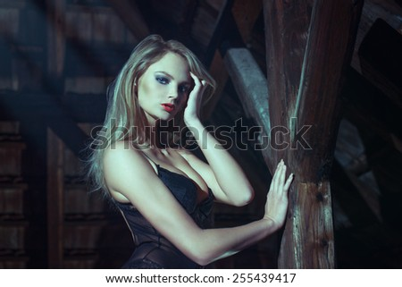 Sexy blonde woman at night in barn, sensuality - stock photo