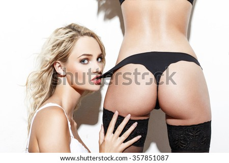 Sexy blonde woman bite lovers panties, lesbian foreplay at white wall - stock photo