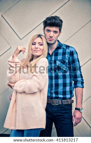Sexy blonde woman feeling good with a handsome blue eyed man on cream background - stock photo