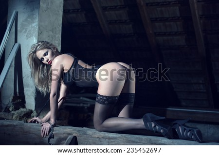 Sexy blonde woman in black underwear kneeling on timber at night - stock photo