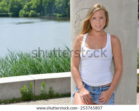 sexy blonde woman in white tank top and denim cut-off shorts standing next to lake in front of pillar - summer - stock photo