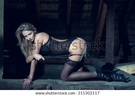 Sexy blonde woman kneeling on timber in barn at night, playing with whip and handcuffs, bdsm - stock photo