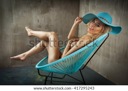 Sexy blonde woman only in hat on chair - stock photo