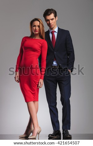 Sexy blonde woman red dress standing next to Young businessman with hands in pockets in studio - stock photo
