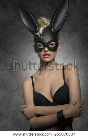 sexy blonde woman with black bra posing in gothic easter portrait with stylish dark bunny mask  - stock photo