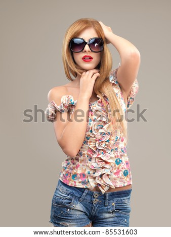 sexy blonde woman with sunglasses and jeans shorts posing - stock photo