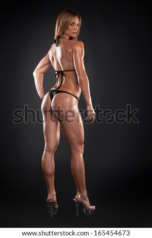 Sexy bodybuilder girl posing to camera. Full length back view isolated over black background  - stock photo