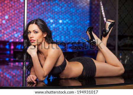 Sexy brunet dancer laying on the stage. Fashion posing in strip club  - stock photo