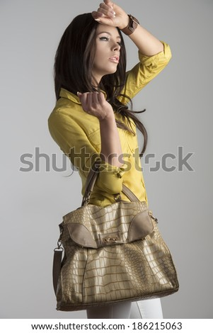 sexy brunette girl in fashion pose taking big vogue bag in the hand and wearing yellow skirt and white pants.  - stock photo