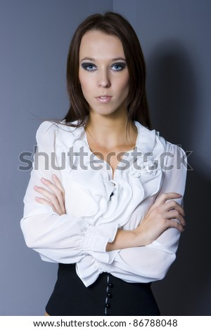Sexy brunette girl in ruffled shirt posing in studio - stock photo