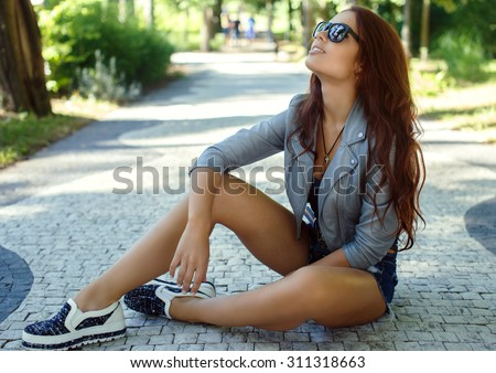 Sexy brunette girl in sunglasses sitting in the park on road from bricks. - stock photo