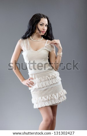 Sexy brunette girl posing for photo on gray background - stock photo