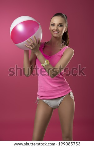 sexy brunette girl with ponytail and pink singlet on bikini playing with fun expression with beach ball  - stock photo