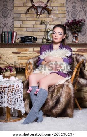 Sexy brunette in grey stockings and purple blouse sitting on the chair - stock photo