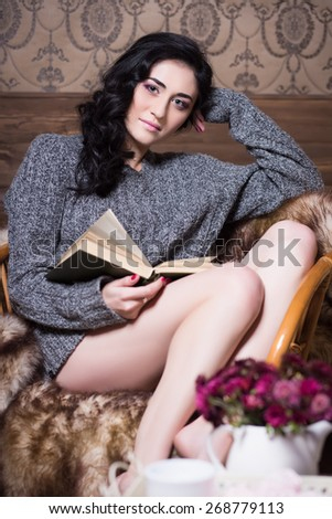 Sexy brunette in grey sweater sitting on the chair with a book - stock photo