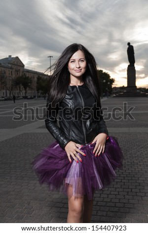sexy brunette 20s russian women outdoors weared black leather jacket and ballet tutu-skirt violet color - stock photo