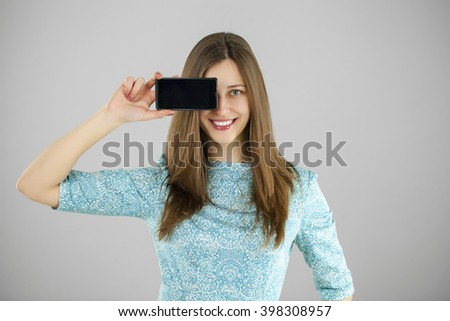 Sexy brunette showing smart phone isolated on gray background - stock photo