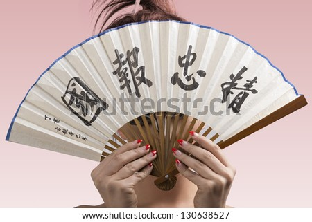 sexy brunette with japan make-up and asian fan, she hides her face behind the fan - stock photo