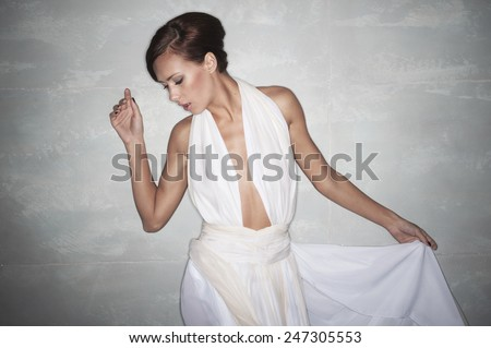 sexy brunette with short hair in an elegant white dress with a deep cut on his chest. with one hand holding the skirt , look down - stock photo
