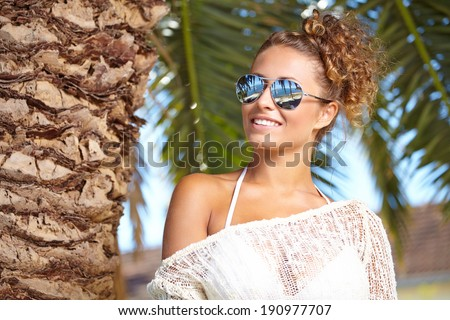 sexy brunette with sunglasses smiling  - stock photo